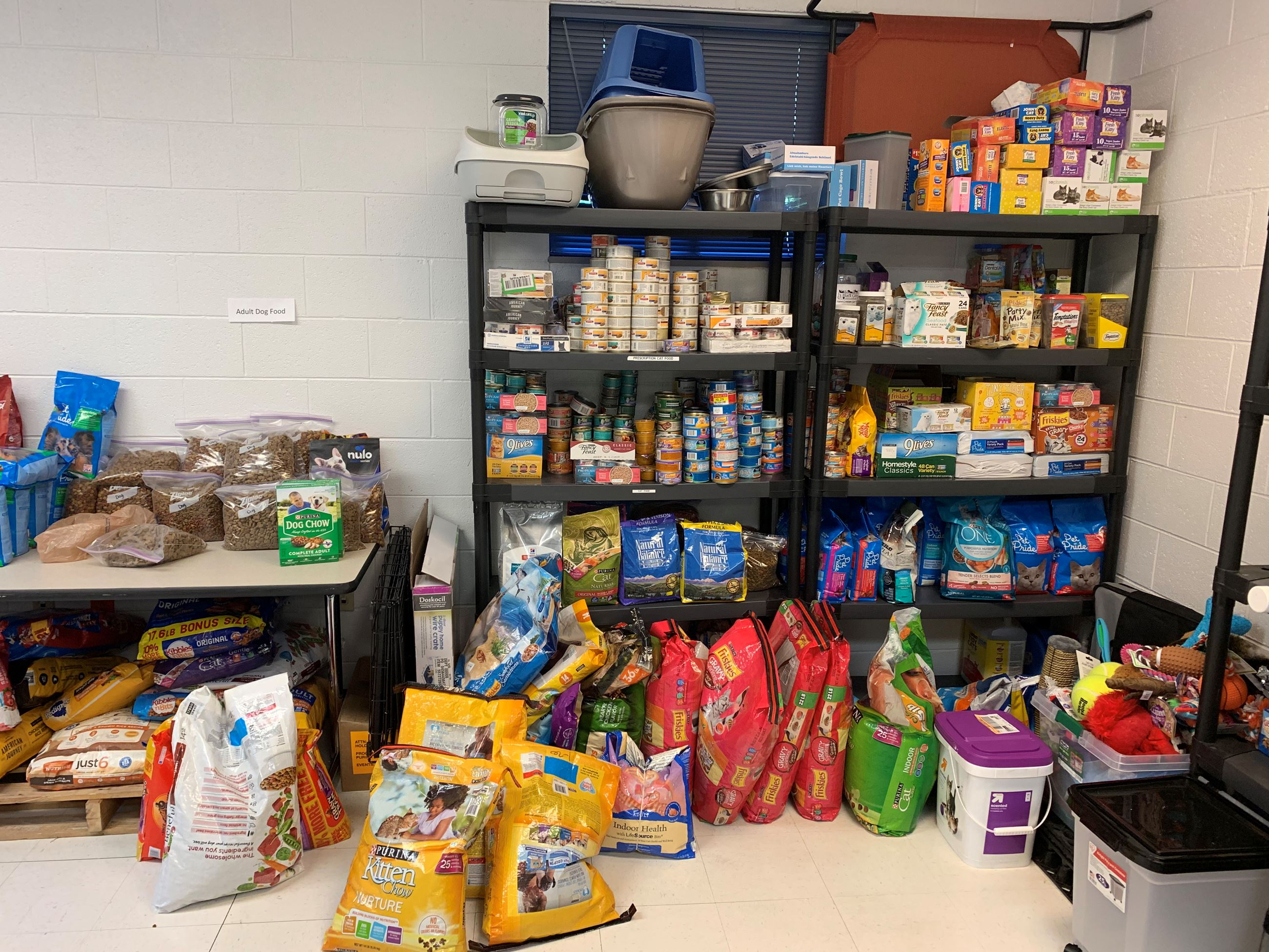 Shelves with donations of pet food.